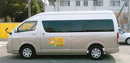 Brown shuttle van with NICONICO Rent a Car logo on the side.