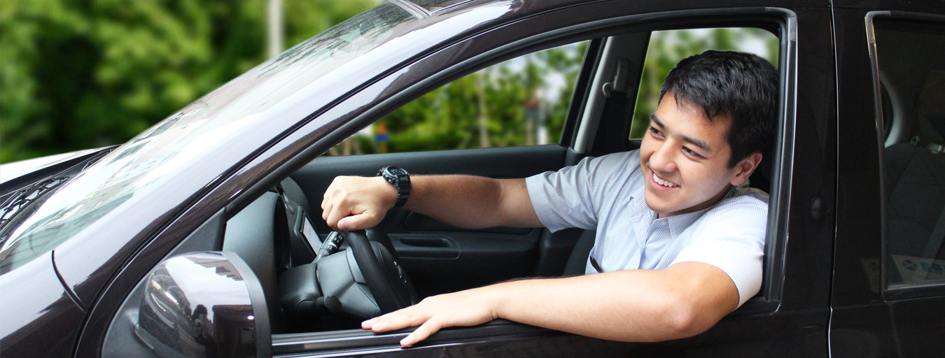 Young man reversing a purple car with his arm sticking out the window.