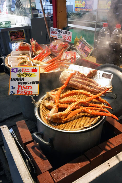 King crab legs being steamed outside of a small seafood shop in Otaru.