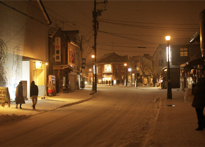 Snowy Otaru village being illuminated by street lamps.
