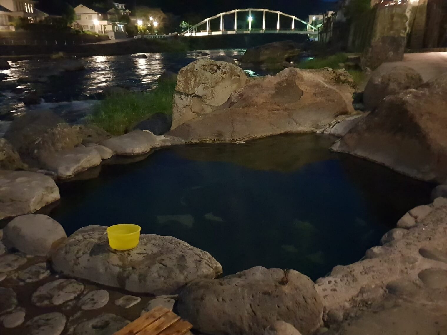 A hot spring pool at night, with a yellow bucket sitting on a rock.