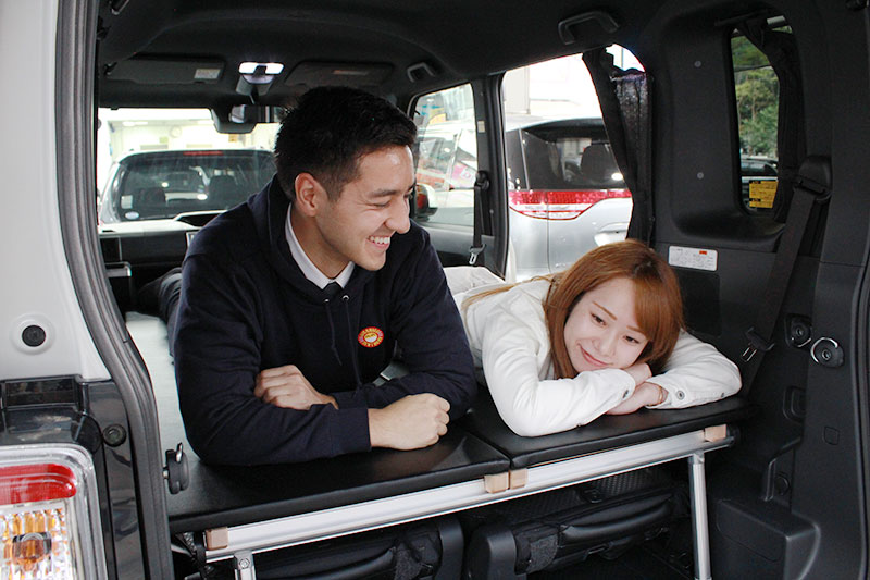 NICONICO Rent a Car Mini Camp Car with two young adults laying down.
