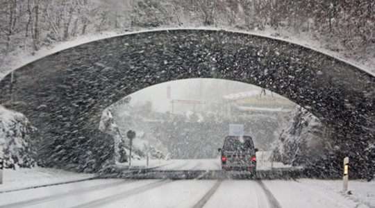 Car driving through tunnel with snow falling in the background.