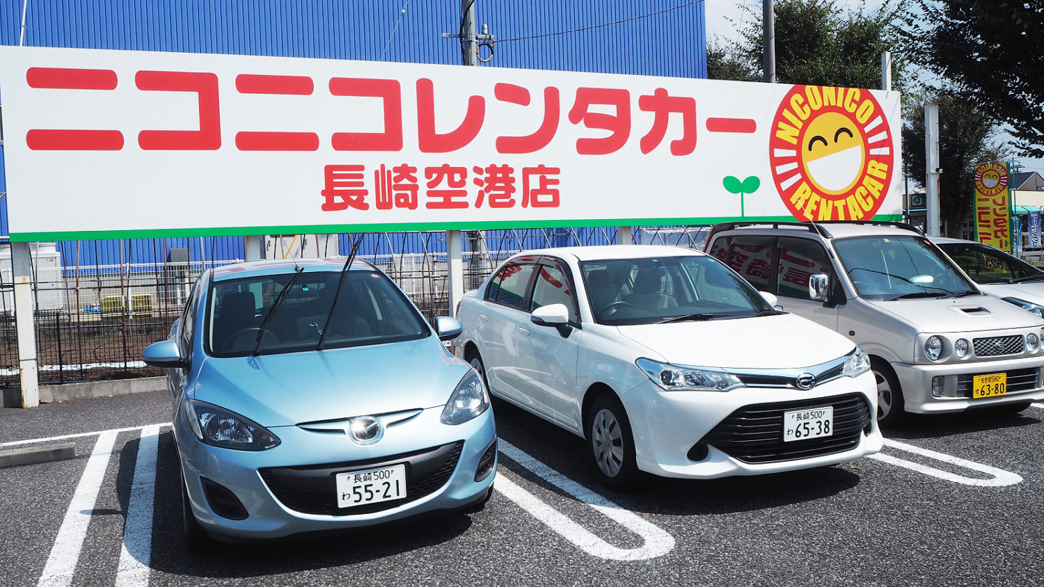 Blue, White, and Red Japanese cars under a NICONICO Rent a Car billboard.