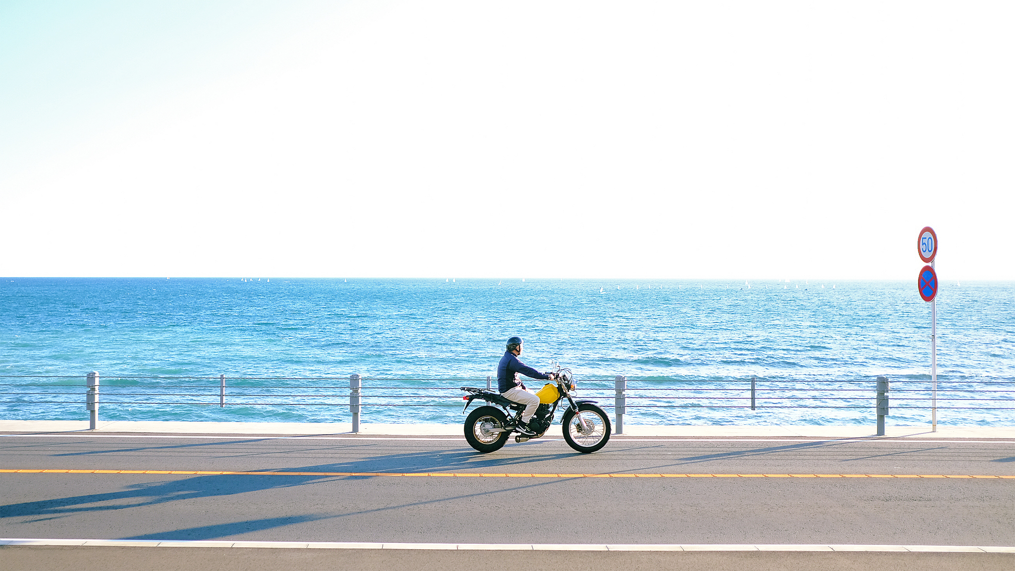 Man riding yellow motorcycle on a road along the beach with blue ocean water and horizon in the background.