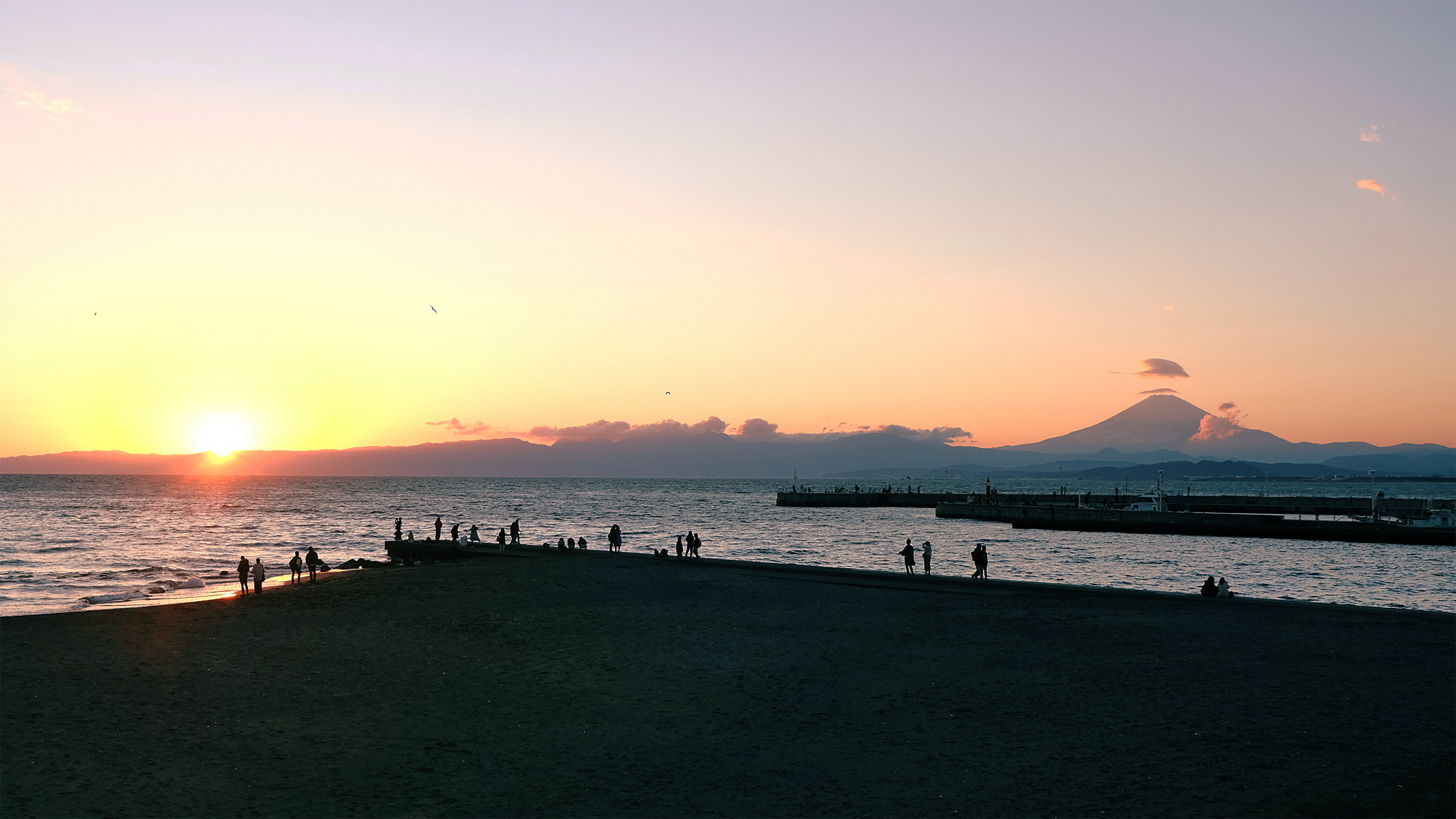 Sunset view of Mt. Fuji with Enoshima beach in the foreground.