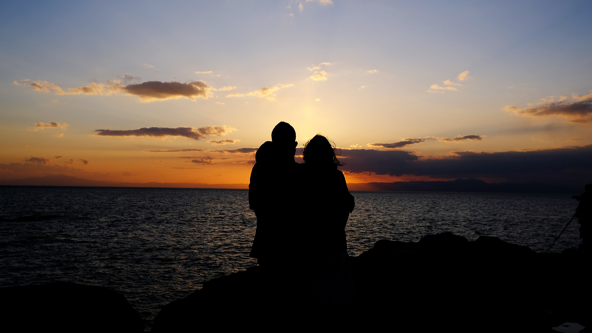 Silhouette of a couple standing on ocean rocks in the sunset.