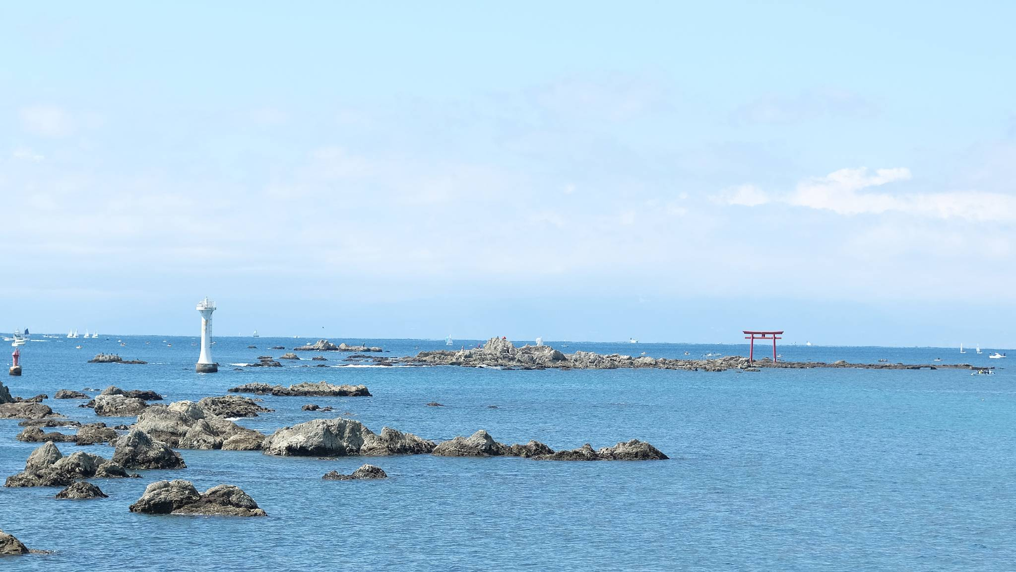 Rocks in the ocean with a red tori gate on one of them.