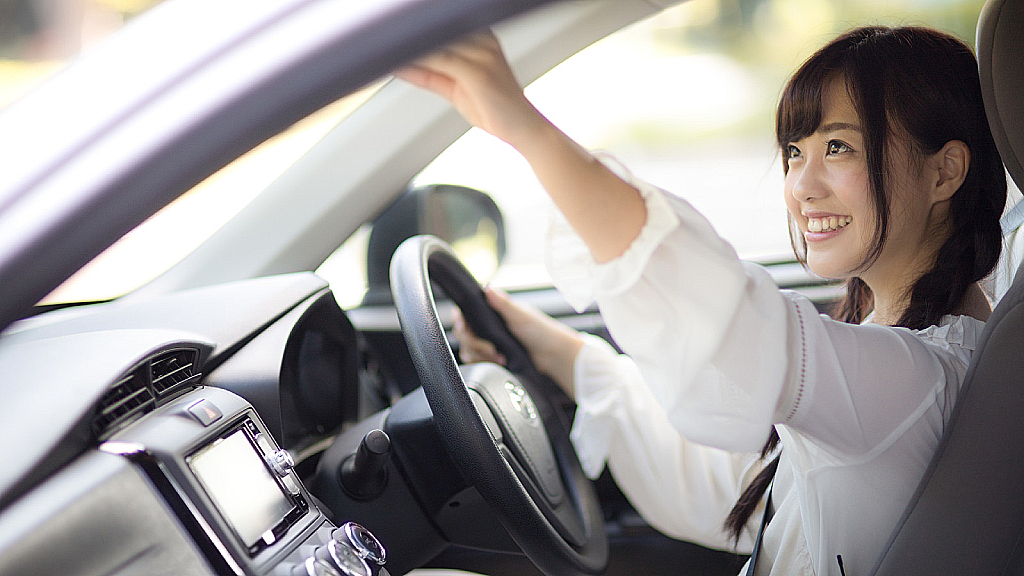 Woman smiling in a Japanese car and adjusting rearview mirror.