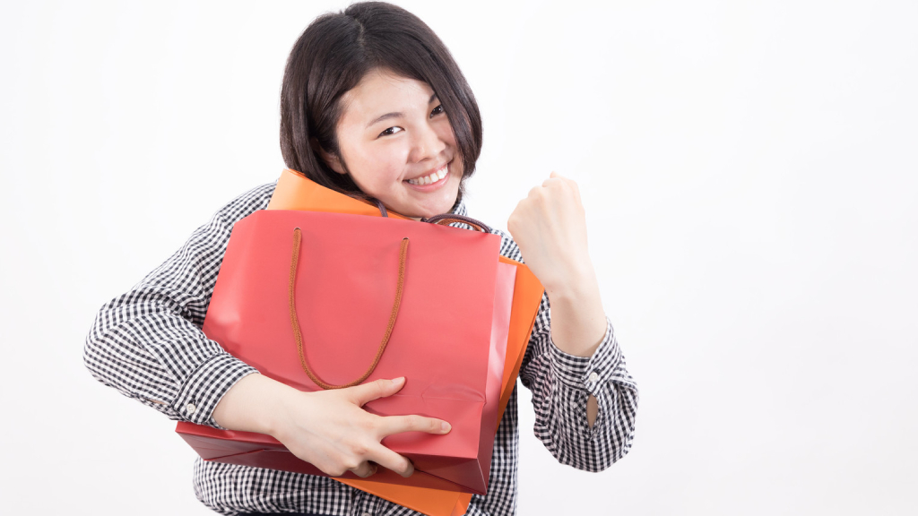 Woman holding two purses and smiling.